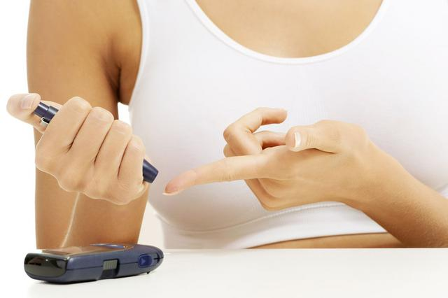 Diabetes patient measuring glucose level blood test with glucometer.